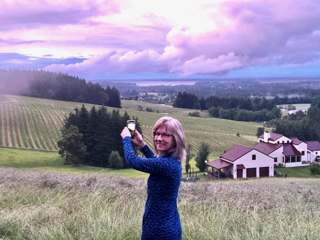 woman looking at view of a vineyard and oregon sky