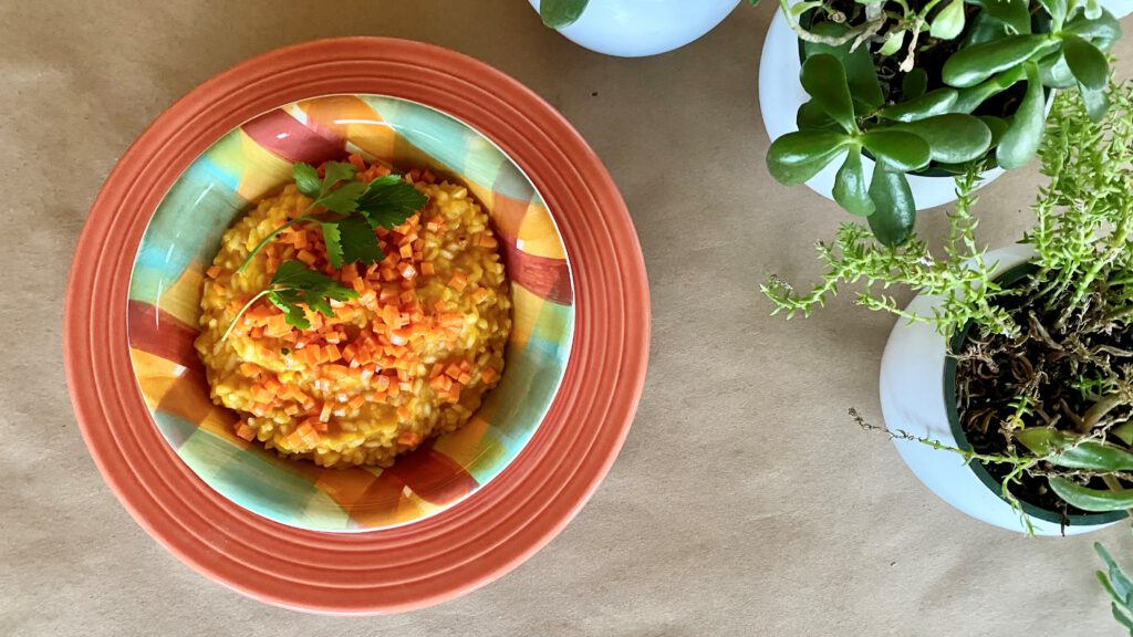 bowl of orange carrot risotto and spring plants
