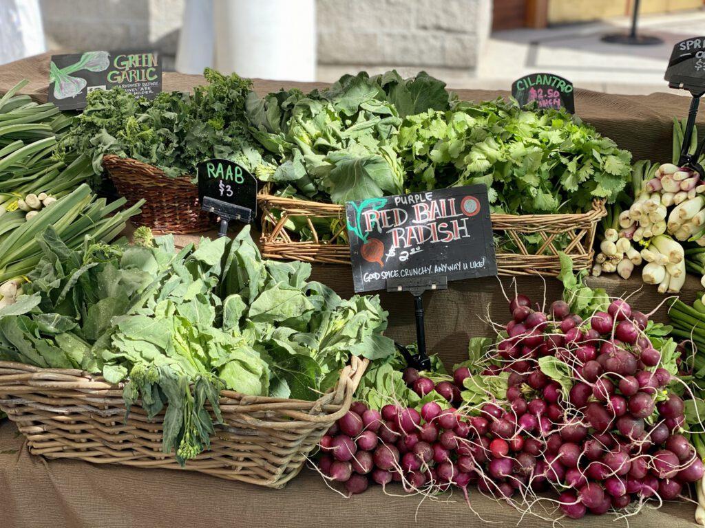 Baskets of greens, garlic, and radishes.