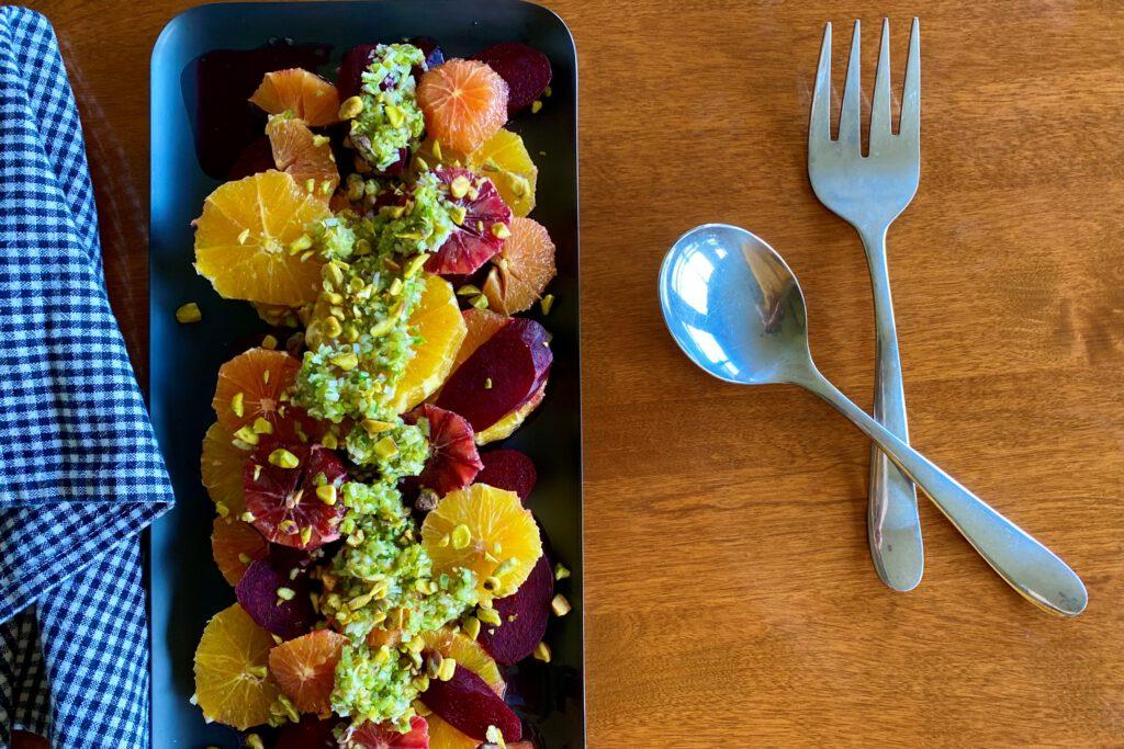 beet and orange salad on black plate with serving utensils