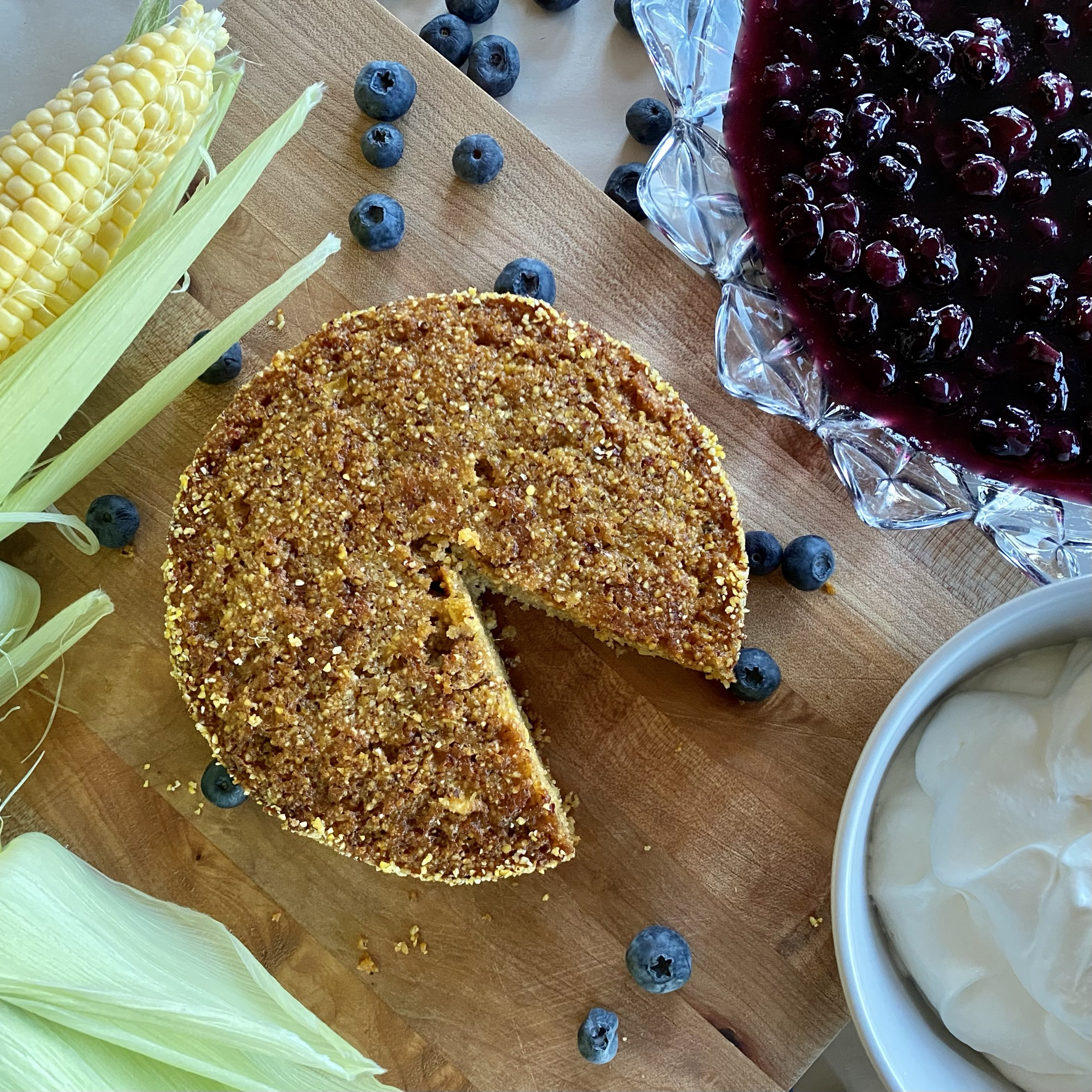 sweet corn buttermilk cake with bowl of blueberry compote