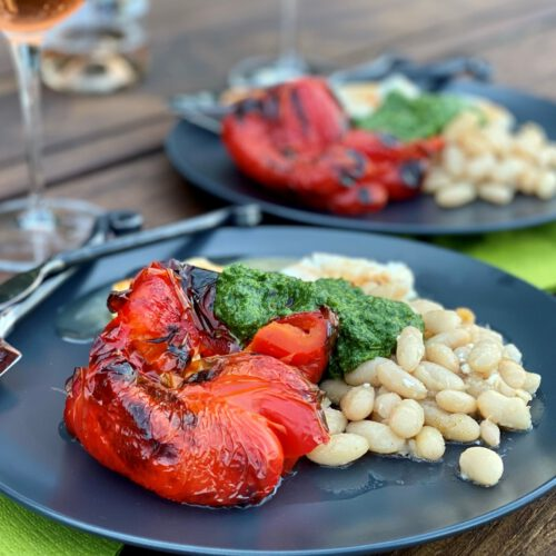 Plates of roasted red peppers, white beans, feta, and green herb sauce.