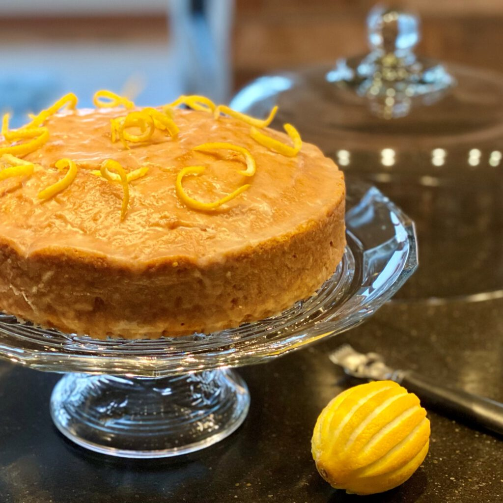 lemon ginger zucchini cake on a cake stand with a lemon next to it.