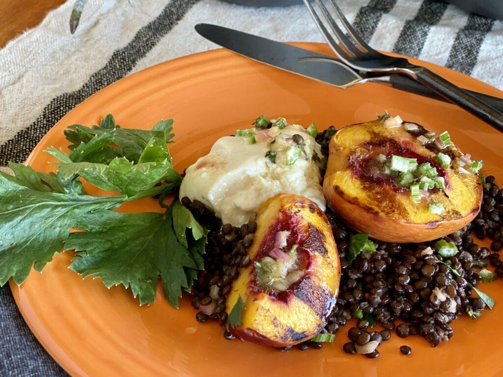beluga lentil, grilled nectarine, and burrata salad arranged on an orange plate.