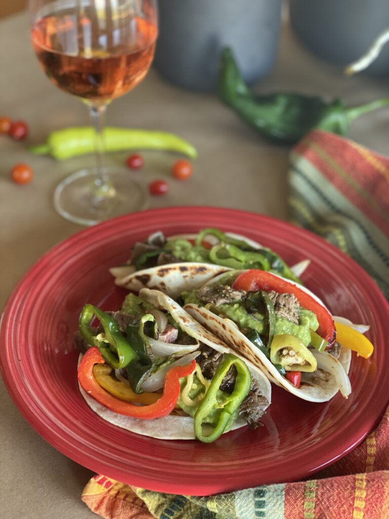 A colorful plate of fajitas and salsa, and a glass of rose.