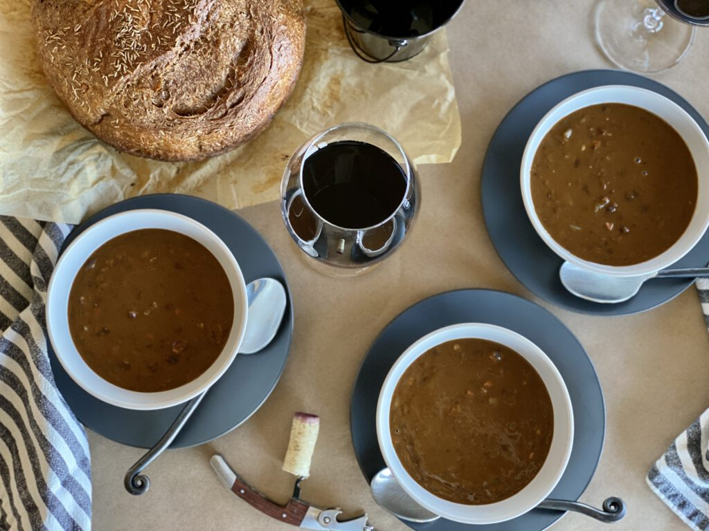 Overhead photo of bowls of pumpkin black bean soup, bread loaf, and wine glasses.