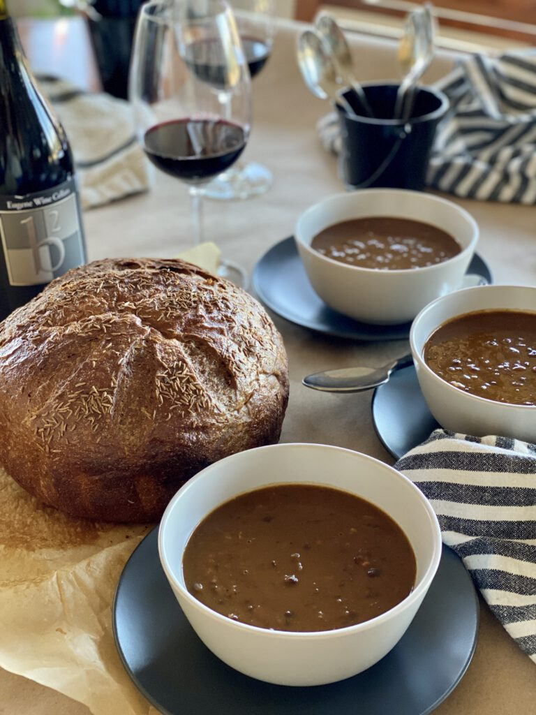 A table set for a party with soup-filled bowls, ine, and a loaf of caraway rye black bread.