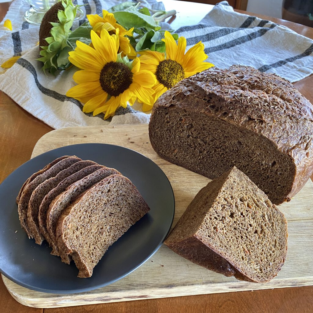 A loaf of caraway rye back bread on a cutting board with sliced and a wedge cut from it.
