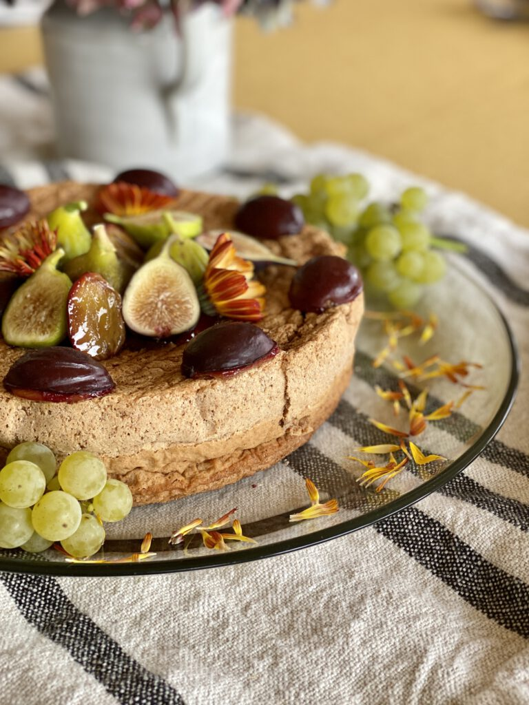 Flourless walnut spice cake adorned with fall fruits and flowers.