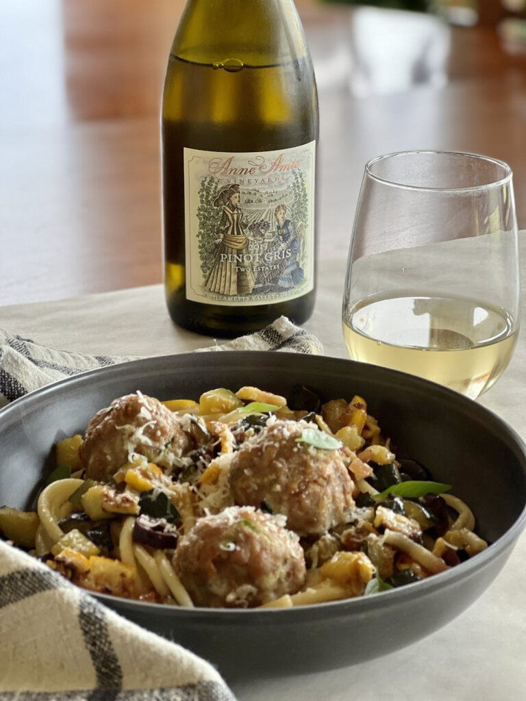 Bowl of Turkey Meatball and Roasted Lemon Zucchini Pasta and glass of wine.