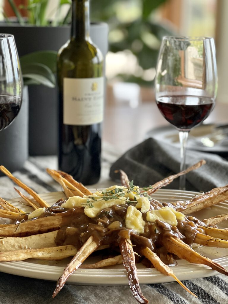 Platter Parsnip Poutine + Rich Mushroom Gravy on table with wine glasses and bottle of wine.